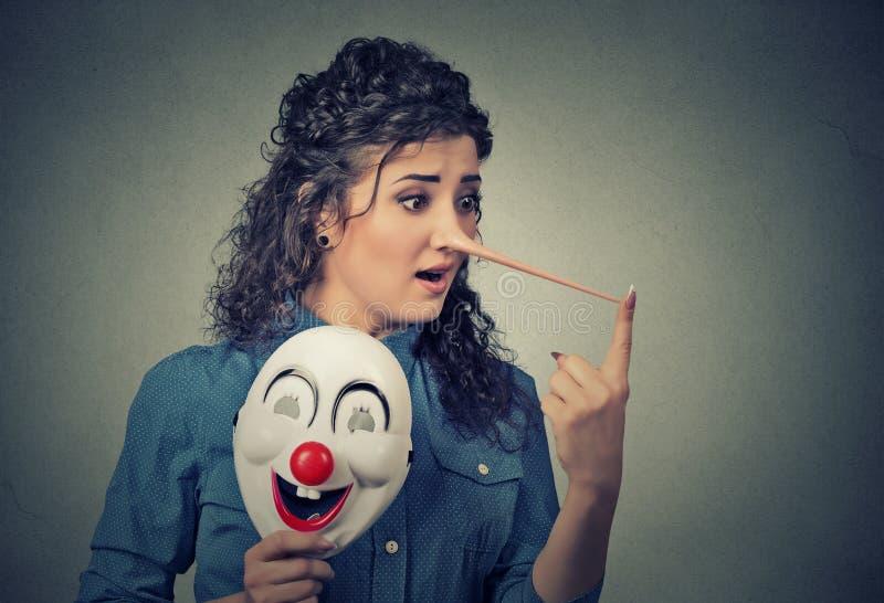 Femme avec le long masque de nez et de clown Concept de menteur image libre de droits