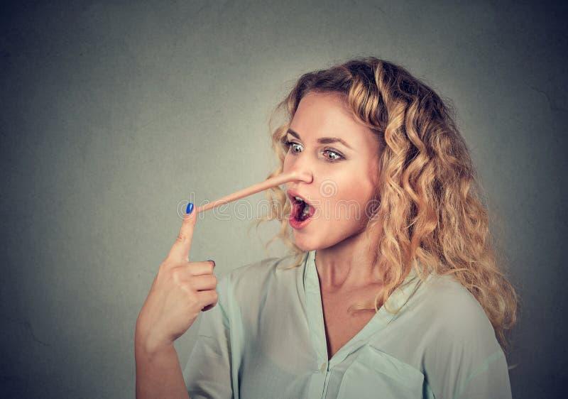 Femme avec le long nez Concept de menteur photographie stock