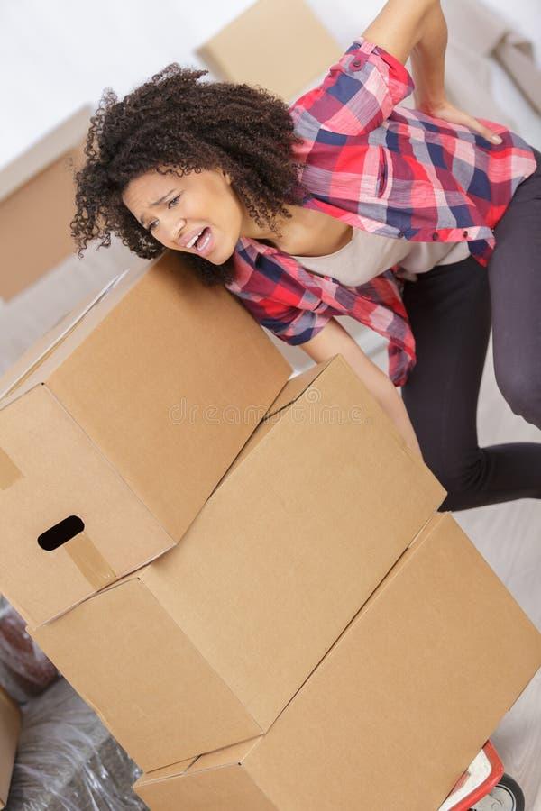 Femme avec le mal de dos tout en soulevant la boîte image libre de droits