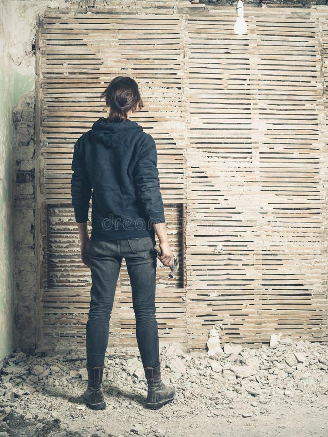 Femme avec le marteau par le mur d'acacia et de barbouillage photographie stock libre de droits