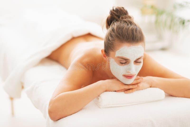 Femme avec le masque de revitalisation sur le visage s'étendant sur la table de massage photographie stock