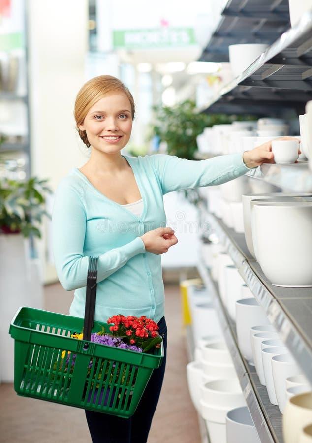 Femme avec le panier choisissant le pot de fleur dans la boutique image stock
