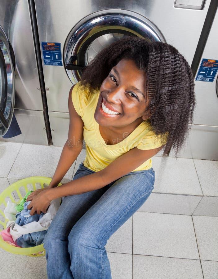Femme avec le panier de blanchisserie près des machines à laver photo stock