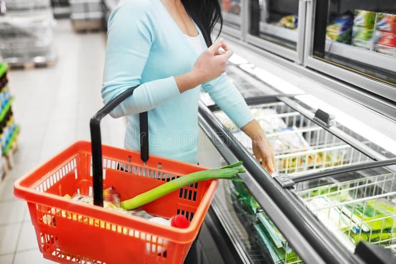 Femme avec le panier de nourriture au congélateur d'épicerie images libres de droits