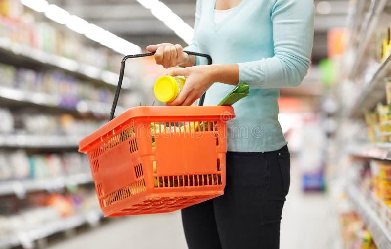 Femme avec le panier de nourriture et pot à l'épicerie images stock