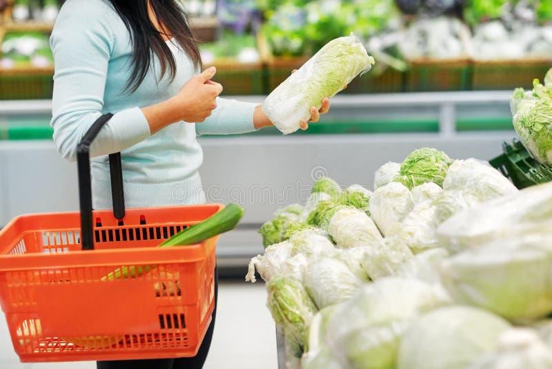 Femme avec le panier et chou de chine à l'épicerie images stock