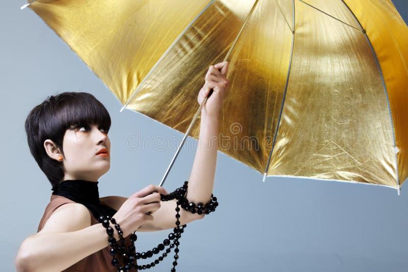 Femme avec le parapluie d'or. image stock