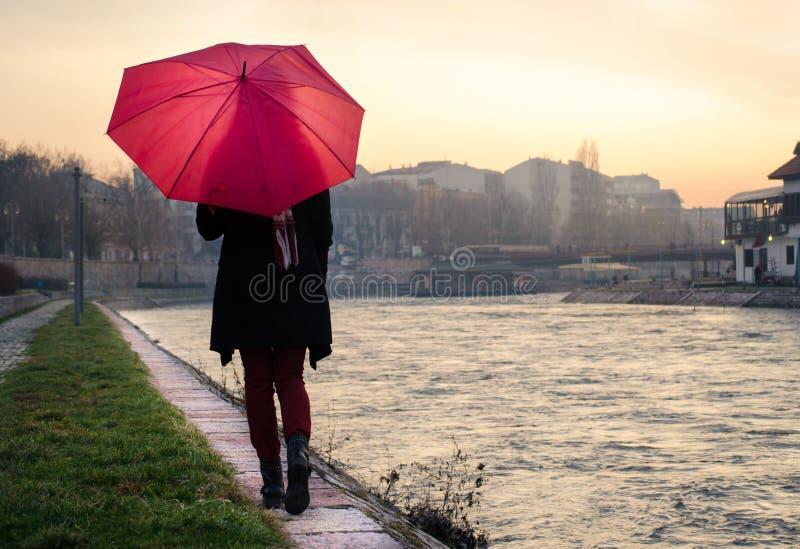 Femme avec le parapluie marchant par la rivière photographie stock libre de droits