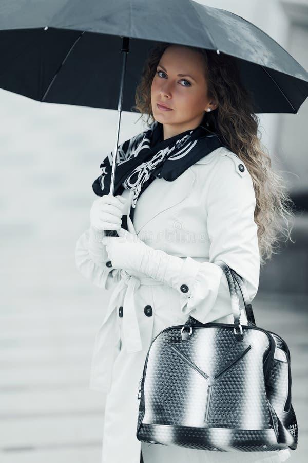 Femme avec le parapluie sous la pluie photographie stock libre de droits