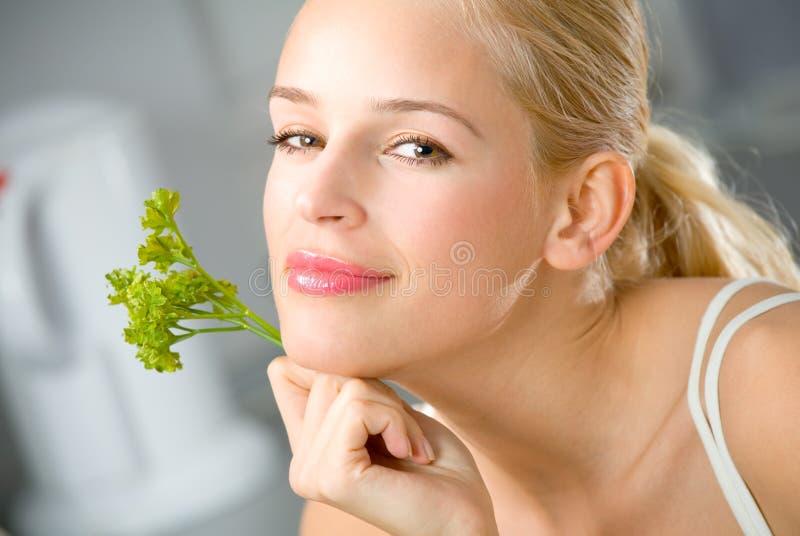 Femme avec le persil à la cuisine photo stock