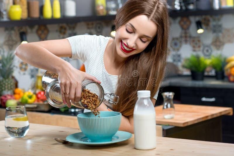 Femme avec le petit déjeuner de granola dans la cuisine image libre de droits