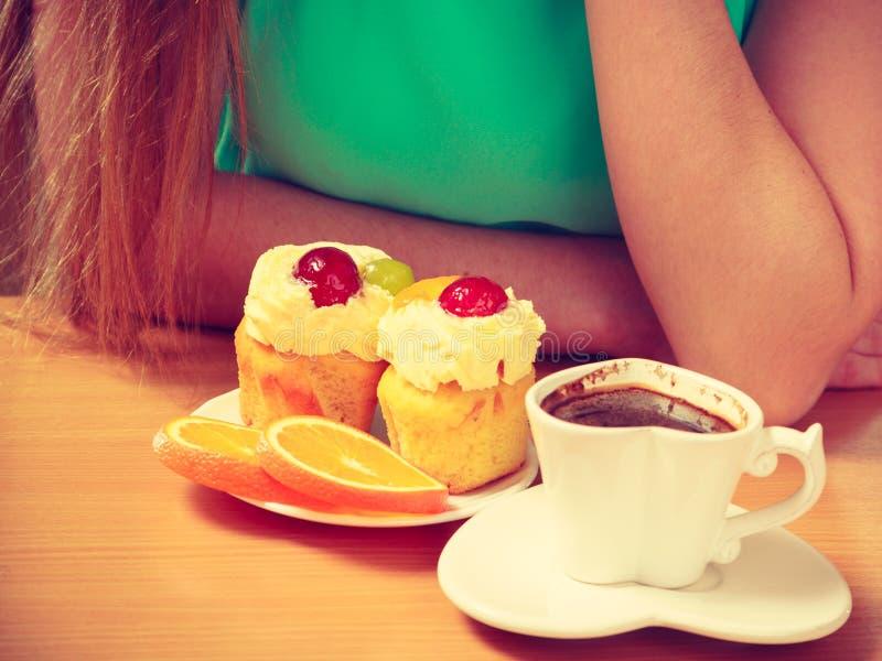 Femme avec le petit gâteau de tasse de café dans la cuisine photo stock