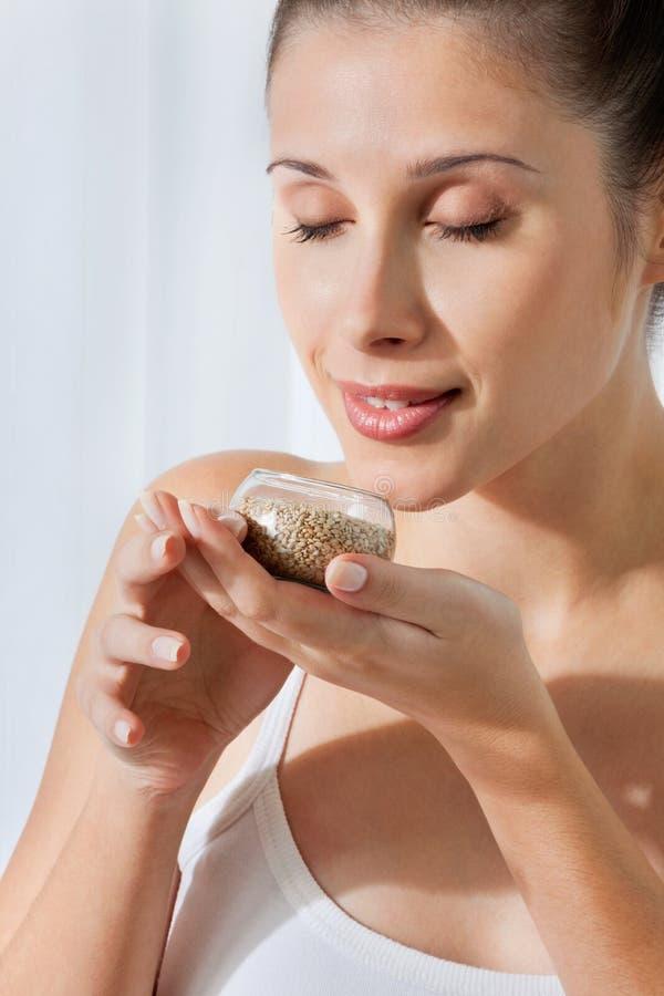 Femme avec le petit pot en verre de graines de lin image stock