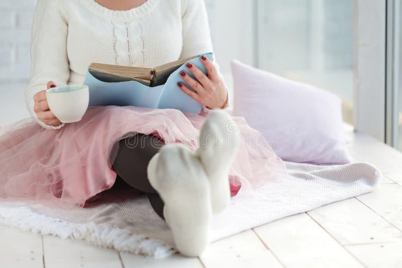 Femme avec le plaid de repos de thé de tasse, pied avec les chaussettes blanches photo stock