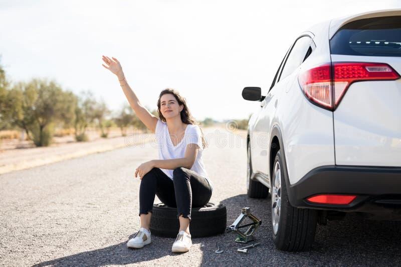 Femme avec le pneu perforé de voiture recherchant l'aide photos stock