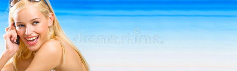Femme avec le portable sur la plage image stock