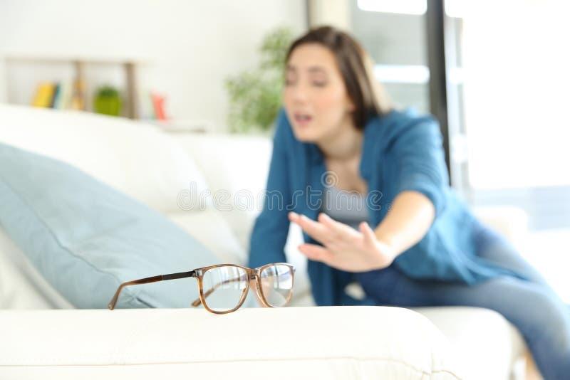 Femme avec le problème de vue recherchant des lunettes photo stock