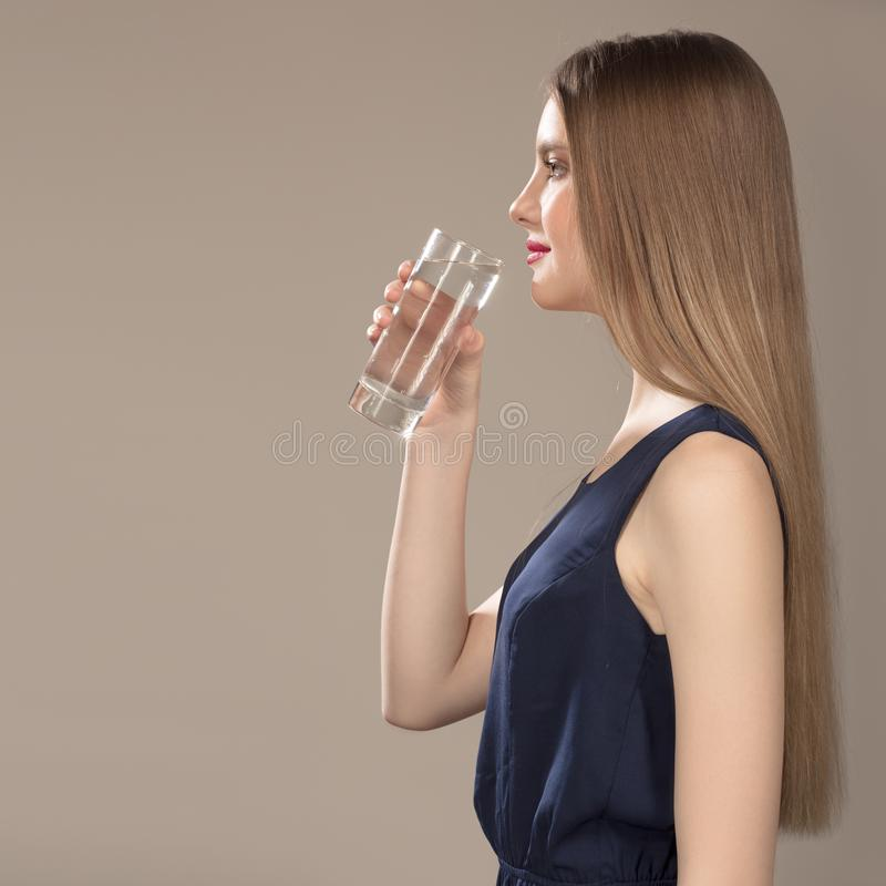 Femme avec le renivellement lumineux Fille de sourire avec de l'eau minéral Apportez un verre de l'eau images stock