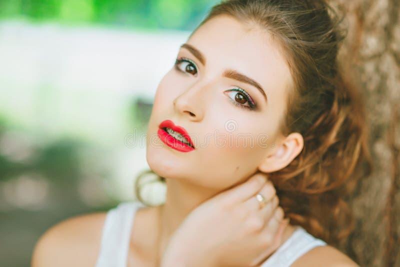 Femme avec le rouge à lèvres rouge et maquillage coloré, portrait en nature Regarder l'appareil-photo images libres de droits