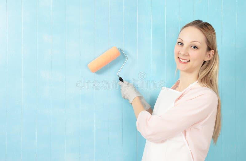 Femme avec le rouleau de peinture image stock