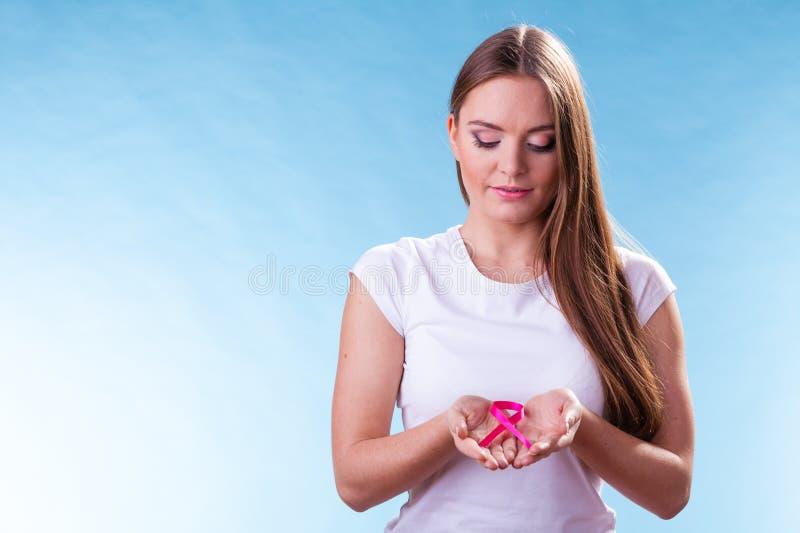 Femme avec le ruban de conscience de cancer du sein sur des mains photographie stock