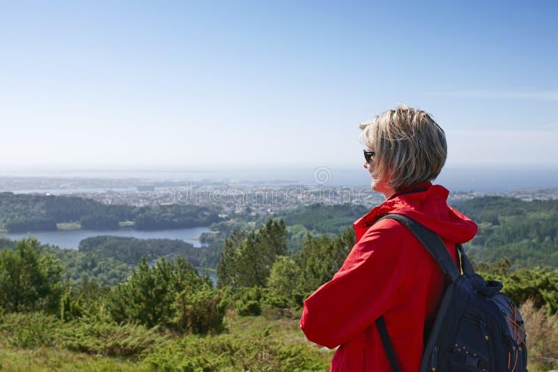 Femme avec le sac à dos appréciant la vue de ville de vallée photo stock