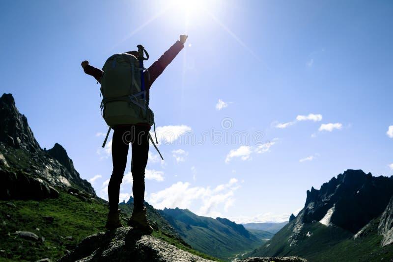femme avec le sac à dos augmentant sur le dessus de montagne de lever de soleil photographie stock