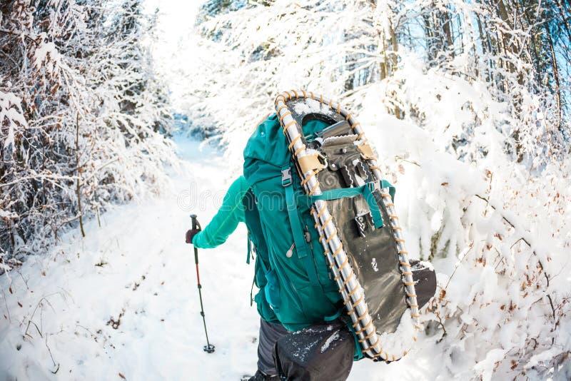 Femme avec le sac à dos et les raquettes dans les montagnes d'hiver images libres de droits