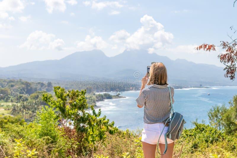Femme avec le sac à dos se tenant sur la falaise de la montagne Île de Bali photographie stock libre de droits