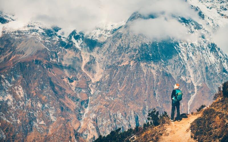 Femme avec le sac à dos sur le chemin et les montagnes photo stock