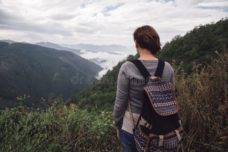 Femme avec le sac à dos tenant les montagnes proches photos stock