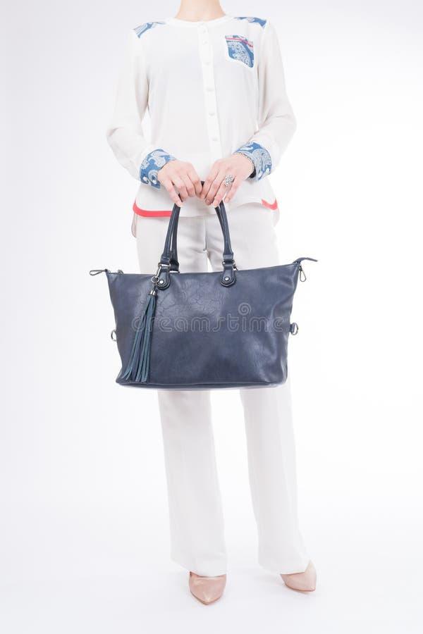 Femme avec le sac à main bleu dans des mains Fond blanc d'isolement photo stock