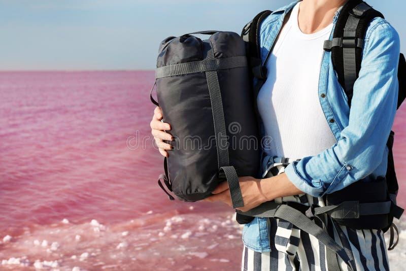 Femme avec le sac de couchage sur la côte photo stock
