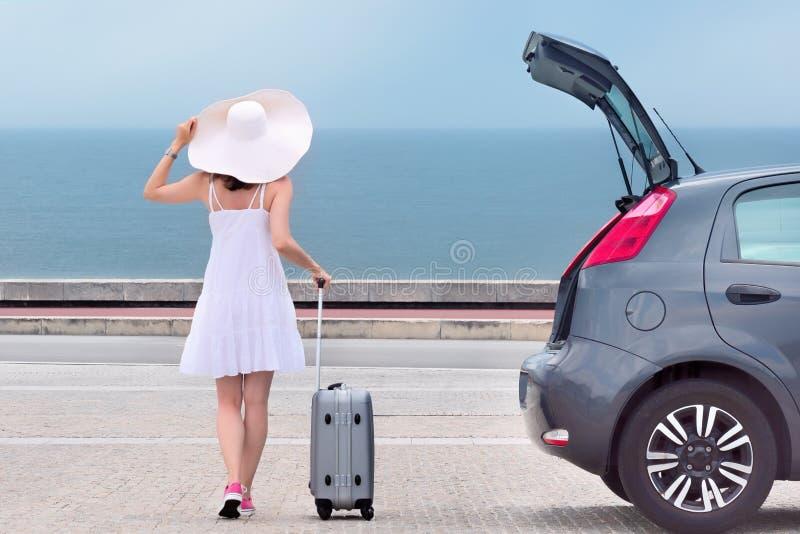 Femme avec le sac de voyage reculant près de la voiture de berline avec hayon arrière photos libres de droits