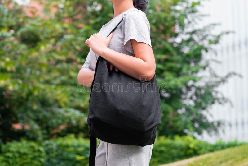 Femme avec le sac vide noir dehors en parc L'espace vide Copiez l'espace photo stock