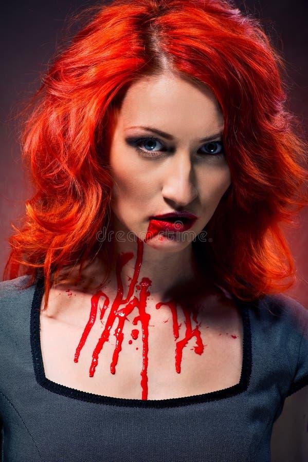 Femme avec le sang dans ses languettes et cou image stock