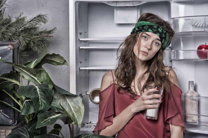 Femme avec le sembler fatigué se tenant à côté du réfrigérateur ouvert Glace de fixation de fille de lait Madame avec les cheveux photographie stock