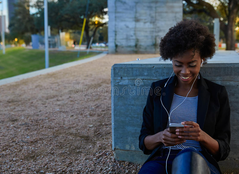 Femme avec le smartphone se reposant en parc images stock