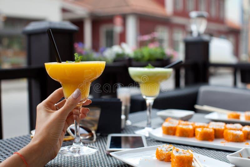 Femme avec le smoothie frais de papaye dans le bar à sushis le jour d'été photos stock