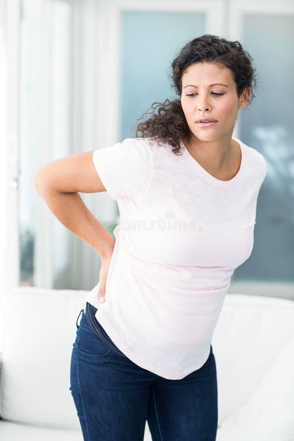 Femme avec le sofa se tenant prêt de douleurs de dos photos stock