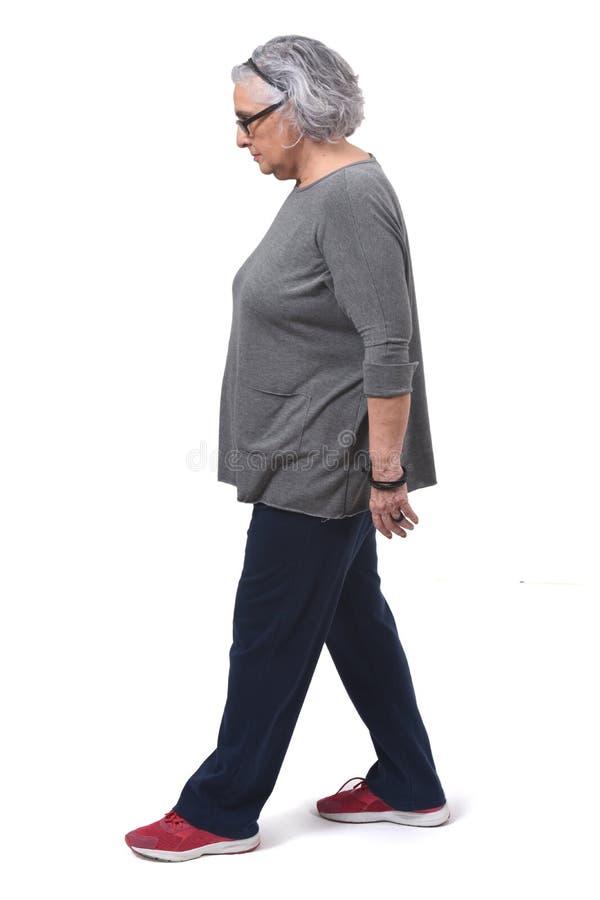 Femme avec le sportsweare marchant sur le fond blanc image stock