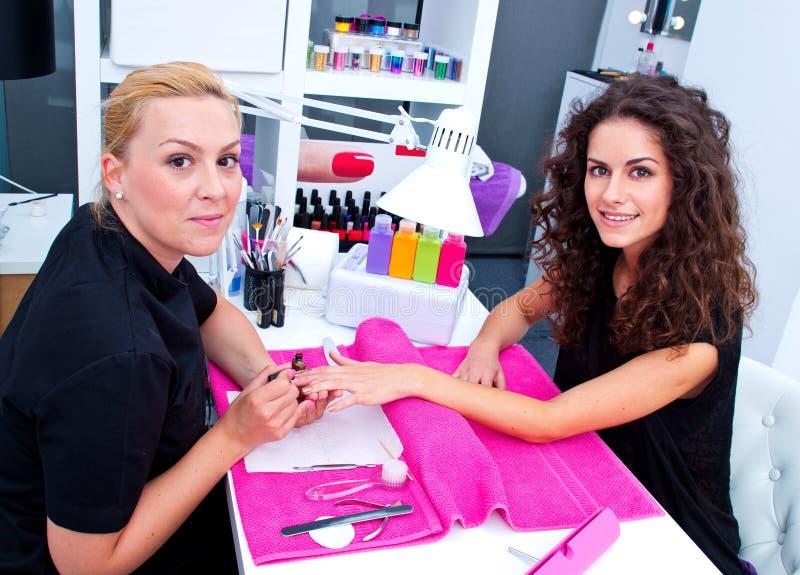 Femme avec le styliste sur la manucure photographie stock libre de droits