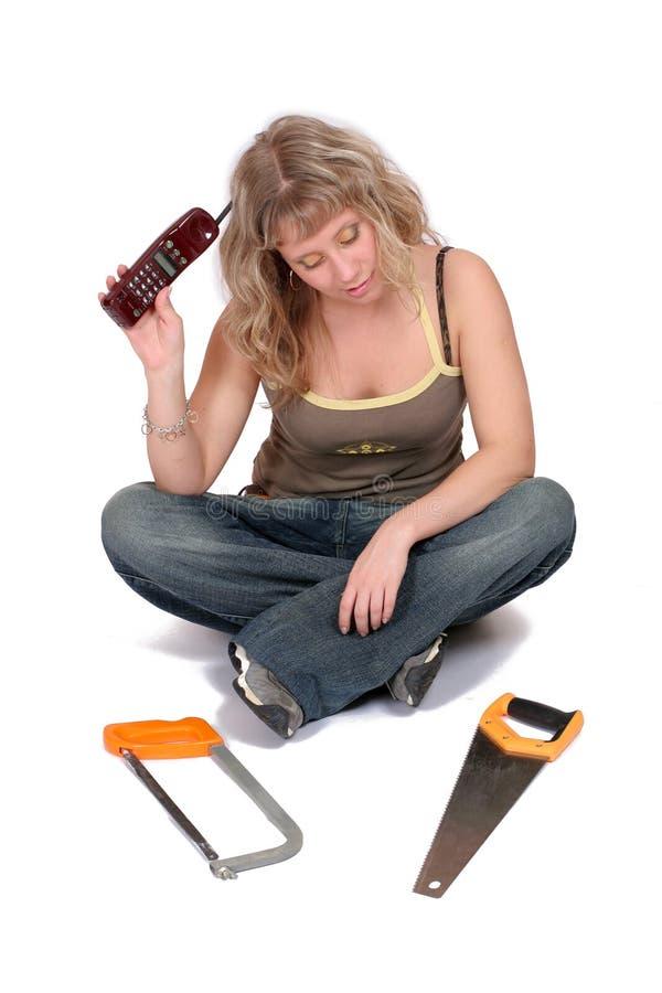 Femme avec le téléphone et la scie photographie stock