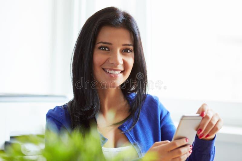 Femme avec le téléphone portable dans le siège social image stock