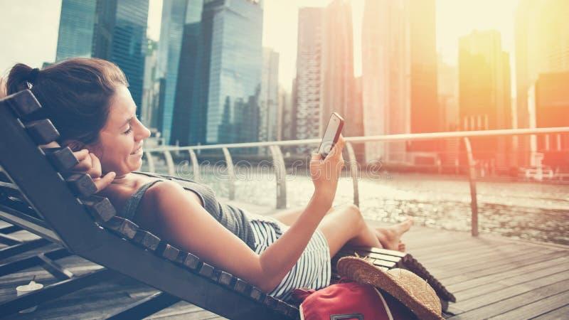Femme avec le téléphone portable se reposant sur la chaise de plate-forme photos libres de droits