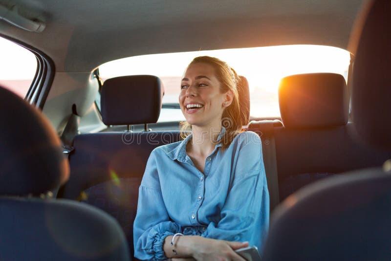 Femme avec le téléphone sur le siège arrière d'une voiture image libre de droits