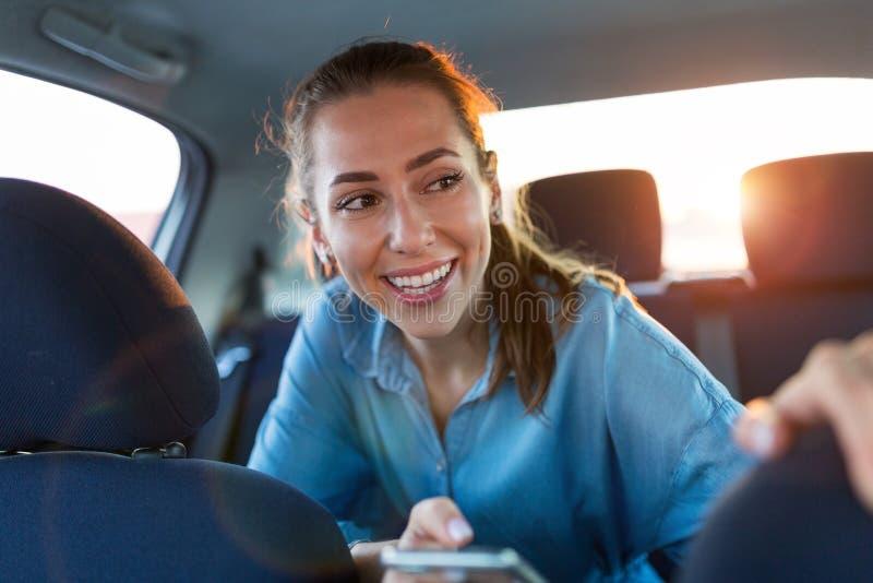 Femme avec le téléphone sur le siège arrière d'une voiture photographie stock