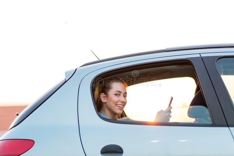 Femme avec le téléphone sur le siège arrière d'une voiture photo libre de droits