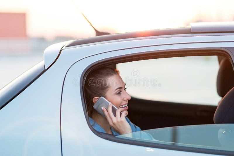 Femme avec le téléphone sur le siège arrière d'une voiture photo stock