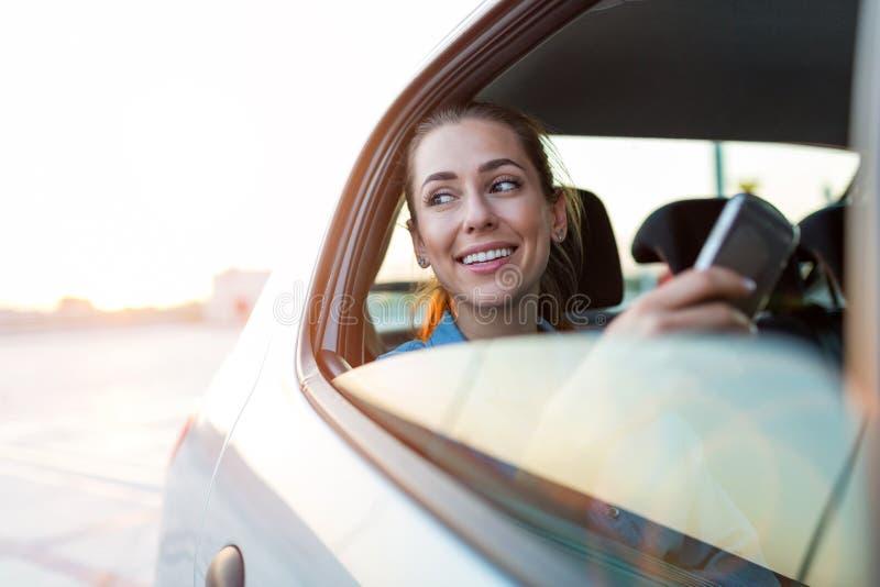 Femme avec le téléphone sur le siège arrière d'une voiture photographie stock libre de droits